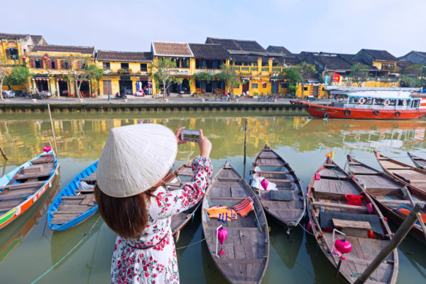 Woman tourist with wearing Vietnamese Non La hat is taking photograph of Ancient heritage Hoi An city during travel in Vietnam.